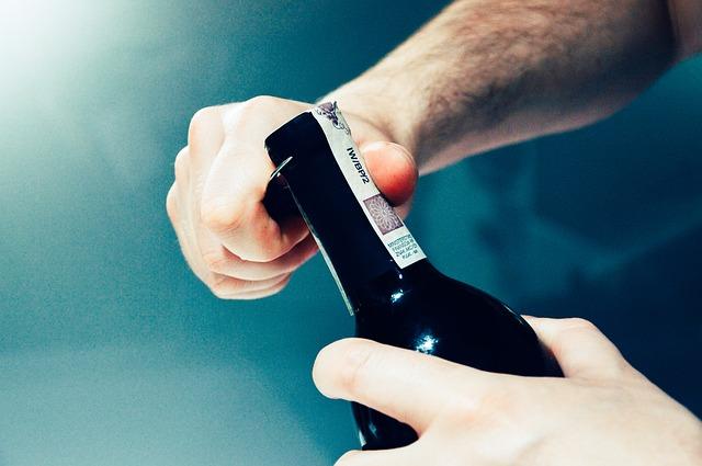男性がビンの栓を抜く画像